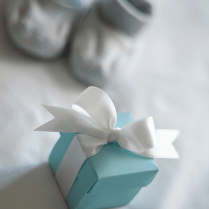 Blue gift box with baby shoes in the background
