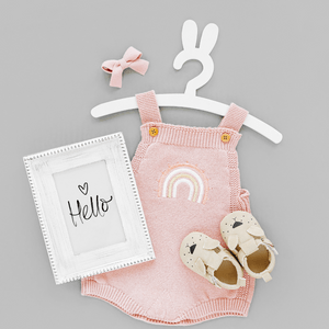 Pretty pink baby dress with beige shoes and a hello sign.