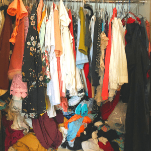 Messy wardrobe with lots of clothes