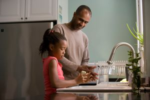 Father and child standing at sink washing their hands. Father looking lovingly at his daughter.