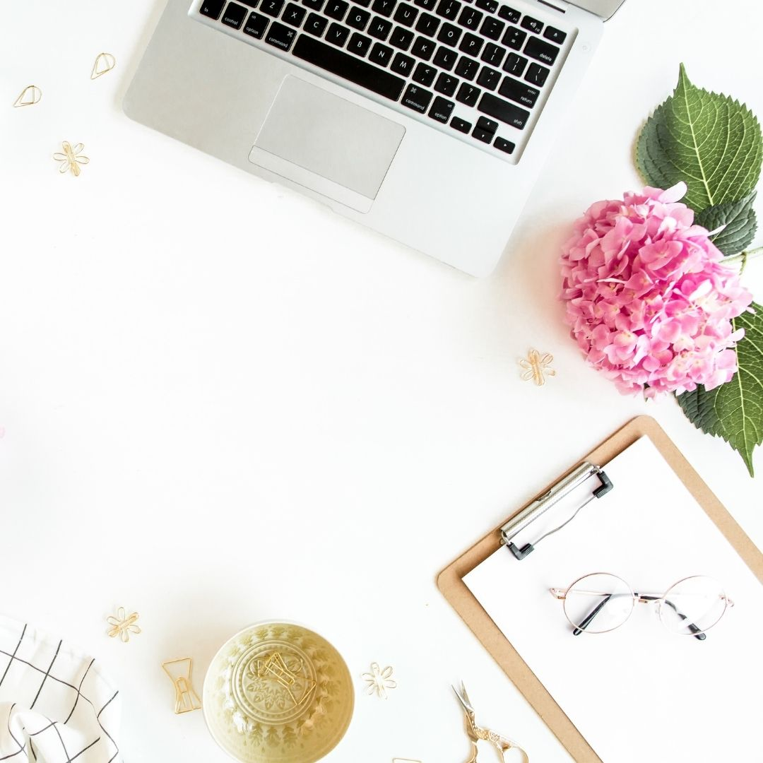 Laptop, pink flowers and a clipboard laid out on a white desk